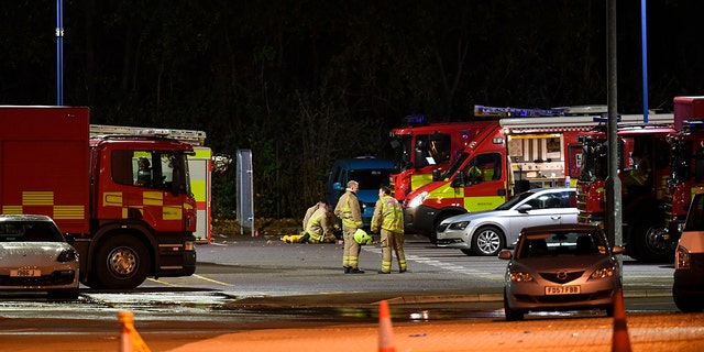 Emergency personnel stand outside the King Power Stadium in Leicester, England after a helicopter belonging to Leicester City Football Club owner Vichai Srivaddhanaprabha crashed in a parking lot. (Joe Giddens/PA via AP)