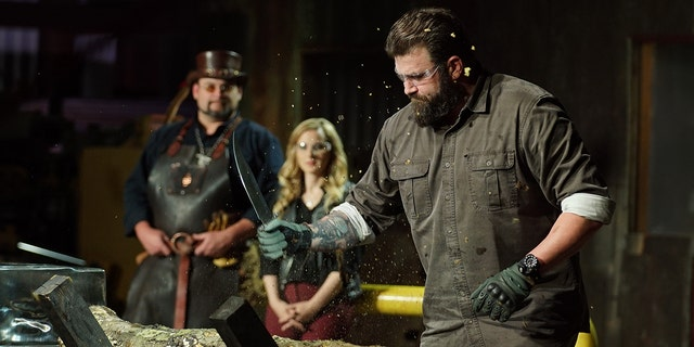 'Mast of Arms' judge Zeke chopping at log with contestants knife. Trent and Ashley in background.