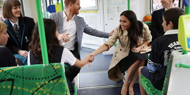 Britain's Prince Harry and Meghan, Duchess of Sussex talk to students while riding on a tram in Melbourne, Australia, Thursday, Oct. 18, 2018. Prince Harry and his wife Meghan are on day three of their 16-day tour of Australia and the South Pacific. ( Chris Jackson/Pool Photo via AP)