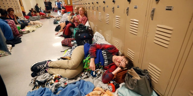 Emily Hindle lies on the floor at an evacuation shelter set up at Rutherford High School, in advance of Hurricane Michael.