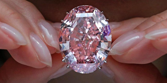 "The ""Pink Star"" diamond, the most valuable cut diamond ever offered at auction, is displayed by a model at a Sotheby's auction room in Hong Kong."