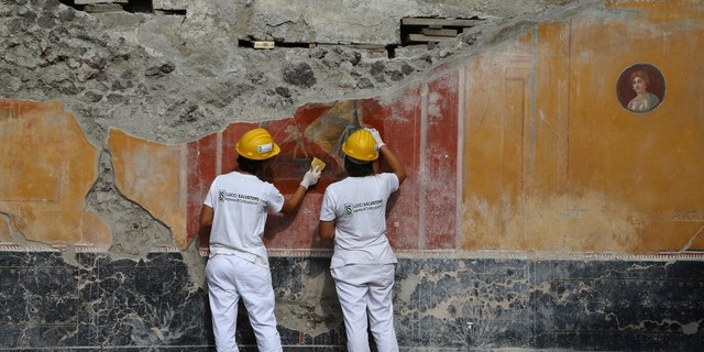 Restorers work on a recently-discovered fresco in the Regio V area of Pompeii.