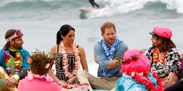 Britain's Prince Harry and Meghan, Duchess of Sussex meet with a local surfing community group, known as OneWave, at Bondi Beach in Sydney, Australia, Friday, Oct. 19, 2018.