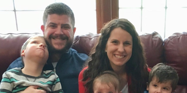 In this Dec. 10, 2017 photo provided by the family, Jon and Kari Kilquist sit with their children, from left, Will, who was born with a list of mysterious symptoms, Emmy and Owen at their home in Murphysboro, Ill.