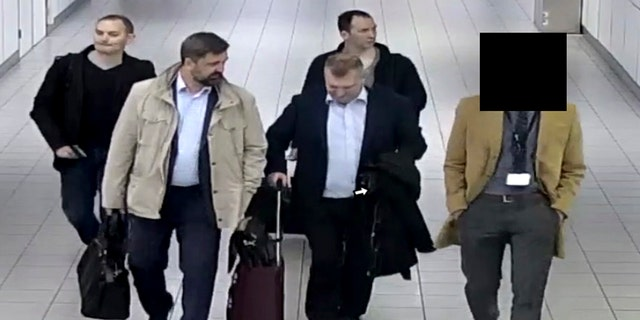 In this image released by the Dutch Defense Ministry, four Russian officers of the Main Directorate of the General Staff of the Armed Forces of the Russian Federation, GRU, are escorted to their flight after being expelled from the Netherlands on April 13, 2018, for allegedly trying to hack into the chemical watchdog OPCW's network.