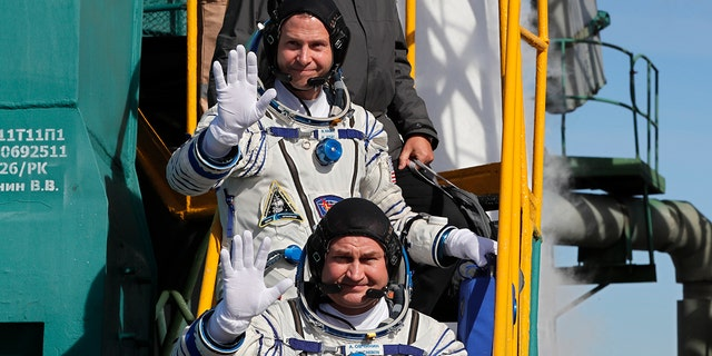 U.S. astronaut Nick Hague, top, and Russian cosmonaut Alexey Ovchinin, crew members of the mission to the International Space Station wave as they board the rocket prior to the launch of Soyuz-FG rocket at the Russian leased Baikonur cosmodrome, Kazakhstan, Thursday, Oct. 11, 2018.
