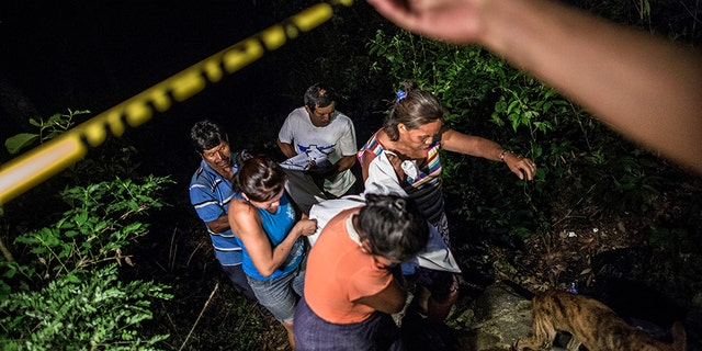 Relatives of a Mara Salvatrucha gang member retrieve his body from a steep gully after he was shot dead in a confrontation with police, in Olocuilta, El Salvador. Two bodies were found at the bottom of the gully following a shootout that began near an old cattle stable, which gang members had turned into a shooting range. El Salvador's homicide rate was 60 per 100,000 inhabitants last year, down from a grisly record of 102 homicides per 100,000 inhabitants in 2015 but still among the highest in the world. (AP Photo/Manu Brabo, File)