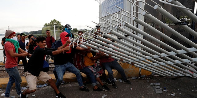 A group of men, part of a caravan of thousands of migrants from Central America en route to the U.S, pulling down a border gate with the intention to carry on their journey, in Tecun Uman, Guatemala.