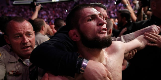 Khabib Nurmagomedov is held back outside of the cage after fighting Conor McGregor in a lightweight title mixed martial arts bout at UFC 229.