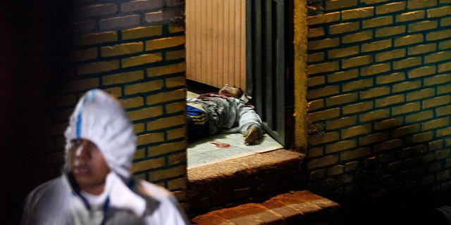 A body is stretched out at the door of a bar in the community of Comayaguela, Honduras, on Friday. At least eight people were killed and two others wounded at the bar that day, police say. (AP Photo/Fernando Antonio)