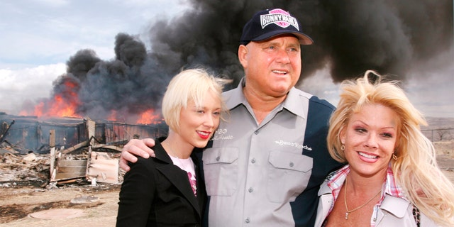 """In this March 25, 2007, file photo, Moonlite Bunnyranch brothel owner Dennis Hof poses with two of his """"working girls"""" Brooke Taylor, left, and a woman working under the name """"Airforce Amy"""", right, as firefighters burn down remains of the former Mustang Ranch 2 brothel east of Reno, Nev."""