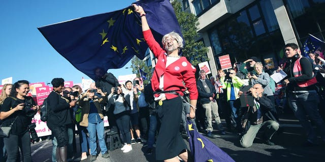 An anti-Brexit campaigner dressed as Theresa May waves European Union flags during the People's Vote March for the Future in London, a march and rally in support of a second EU referendum, in London, Saturday Oct. 20, 2018. Thousands of protesters gathered in central London on Saturday to call for a second referendum on Britain's exit from the European Union.