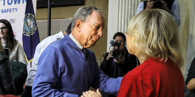 Former New York Mayor Michael Bloomberg talks to a woman who lost her daughter to gun violence after speaking at a rally at City Hall in Nashua, New Hampshire, on Saturday.