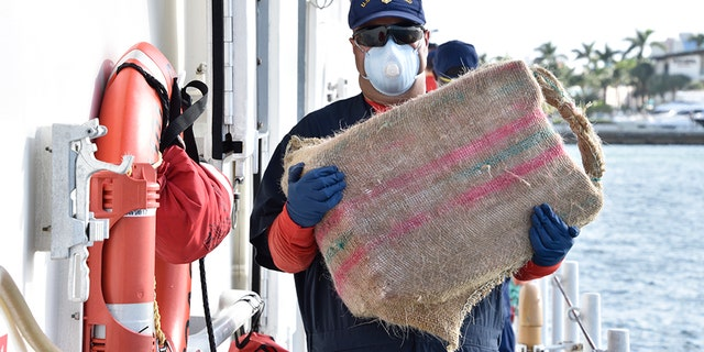 """Photos provided by the Coast Guard showed """"bales of cocaine"""" as they were being unloaded from the vessel."""