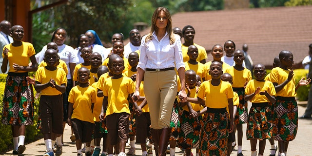 First lady Melania Trump walks with singing children as she visits the Nest Orphanage in Limuru, Kenya, Friday, Oct. 5
