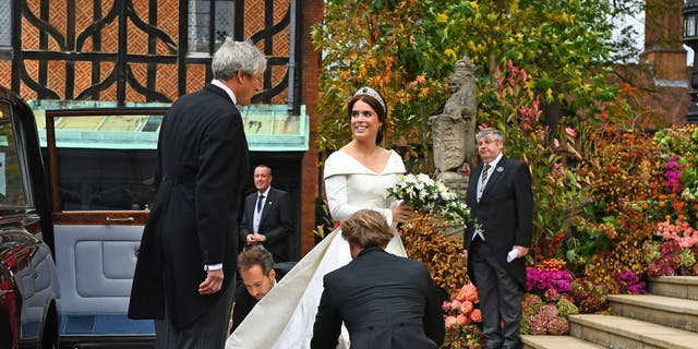 Britain's Princess Eugenie arrives with her father Prince Andrew for her wedding to Jack Brooksbank at St George's Chapel, Windsor Castle, near London, England, Friday Oct. 12, 2018. (Victoria Jones/Pool via AP)