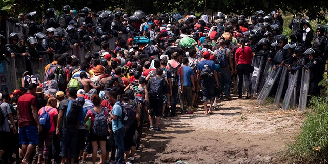 A new group of Central American migrants are met by Mexican Federal Police after the migrants waded in mass across the Suchiate River, that connects Guatemala and Mexico, in Tecun Uman, Guatemala.