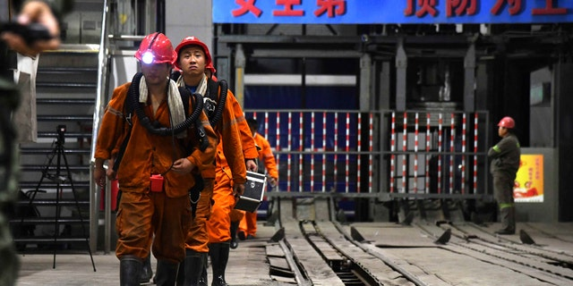 In this photo taken Oct. 21, 2018 and released by Xinhua News Agency, rescuers walk out of the site of a coal mine where falling rocks killed miners and trapped some in Yuncheng County in eastern China's Shandong Province.