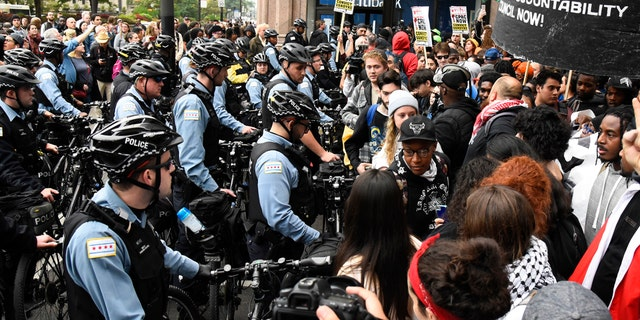 Protesters stand near police in the downtown area after a jury convicted white Chicago police officer Jason Van Dyke of second-degree murder in the 2014 shooting of black teenager Laquan McDonald Friday, Oct. 5, 2018, in Chicago.