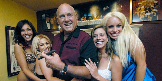 """In this June 26, 2008, file photo, owner Dennis Hof poses with some of his """"working girls"""" in the parlor of his Moonlite BunnyRanch in Mound House, east of Carson City, Nev."""