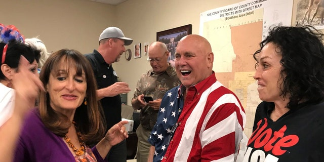In this June 12, 2018, file photo, Nevada brothel owner Dennis Hof, second from right, celebrates with Heidi Fleiss, right, and others after winning the primary election in Pahrump, Nev.