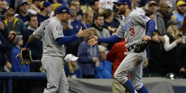 Los Angeles Dodgers' Chris Taylor is congratulated by Manny Machado after catching a ball hit by Milwaukee Brewers' Christian Yelich during the fifth inning of Game 7 of the National League Championship Series baseball game Saturday, Oct. 20, 2018, in Milwaukee.
