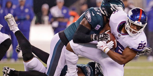 New York Giants running back Saquon Barkley (26) is tackled by Philadelphia Eagles' Malcolm Jenkins (27) during the first half of an NFL football game Thursday, Oct. 11, 2018, in East Rutherford, N.J. (AP Photo/Julio Cortez)