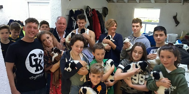 A litter of 14 pups orphaned when their mother died giving birth have been saved after they were hand reared - by an entire village.