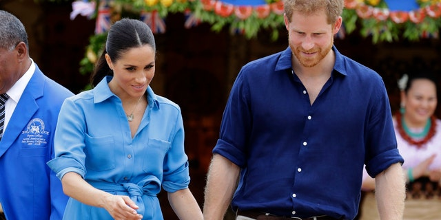 Britain's Prince Harry and Meghan, Duchess of Sussex smile during a visit to Tupou College in Tonga, Friday, Oct. 26, 2018.