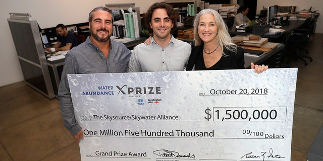 The Skysource/Skywater Alliance co-founders David Hertz, left, his wife Laura Doss-Hertz, right, and project designer Willem Swart pose for a photo with an image of a $1.5 million prize the company received Wednesday in Los Angeles.