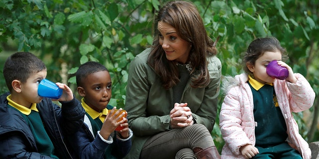 Catherine, Duchess of Cambridge sits on a log with children during a visit to Sayers Croft Forest School and Wildlife Garden on Oct. 2, 2018 in London. Sayers Croft is an activity center aimed at educating and involving children and the local community in the environment.