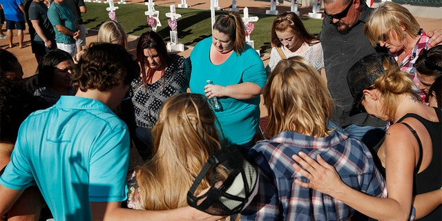 People pray at a makeshift memorial for victims of the Las Vegas shooting Sunday in Las Vegas.