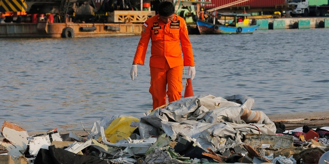 A member of Indonesian Search and Rescue Agency (BASARNAS) inspects debris recovered from near waters where a Lion Air passenger jet crashed off, at Tanjung Priok Port in Jakarta, Indonesia Monday, Oct. 29, 2018.