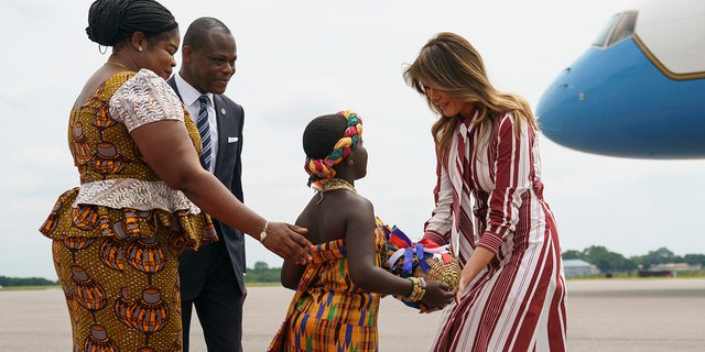 First lady Melania Trump accepts flowers from flower girl Lillian Naa Adai Sai, 8, as she receives flowers as she arrives at Kotoka International Airport in Accra, Ghana, Tuesday, Oct. 2