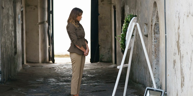 "First lady Melania Trump pauses after placing a wreath near at one of the dungeon doors at Cape Coast Castle in Cape Coast, Ghana, Wednesday, Oct. 3. Cape Coast Castle was a ""slave castle"" used in the trans-Atlantic slave trade. Behind her is the ""Door of No Return."""