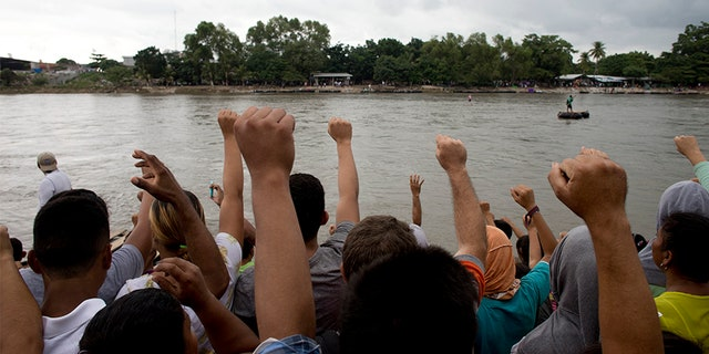Honduran migrants sing their national anthem standing at the shore of the Suchiate river on the border between Guatemala and Mexico.