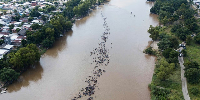 A group of Central American migrants bound for the U.S border wade in mass across the Suchiate River, that connects Guatemala and Mexico, in Tecun Uman, Guatemala.