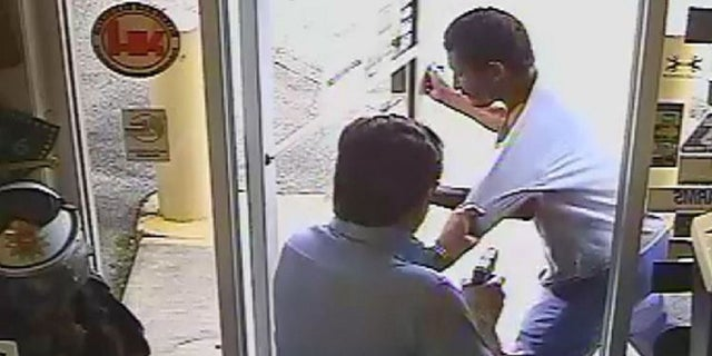 Lakeland Commissioner Michael Dunn holds a gun in his right hand while trying to keep Cristobal Lopez from carrying a hatchet out of his store on Oct. 3.