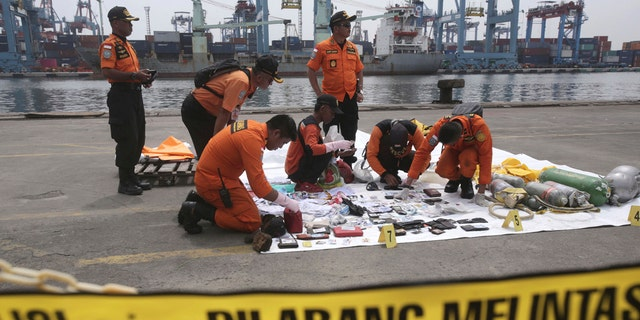 Rescuers examine personal belongings of passengers of a crashed Lion Air plane recovered from the waters near where the passenger jet is believed to have crashed, at Tanjung Priok Port in Jakarta, Indonesia, Tuesday, Oct. 30, 2018.