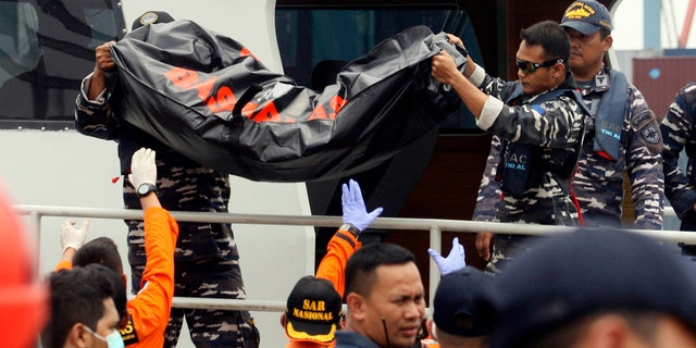 Rescuers remove a body bag containing the remains the area where a Lion Air plane is suspected to crash, upon arrival at Tanjung Priok Port in Jakarta, Indonesia.