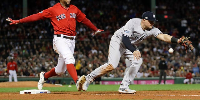New York Yankees first baseman Luke Voit, right, fails to hang on to the throw after a single by Boston Red Sox's Xander Bogaerts during the fifth inning of Game 1 of the American League Division Series, in Boston, Oct. 5, 2018.
