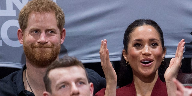 Britain's Prince Harry and Meghan, Duchess of Sussex applaud as they watch the wheelchair basketball final at The Invictus Games in Sydney, Australia, Saturday, Oct. 27, 2018.