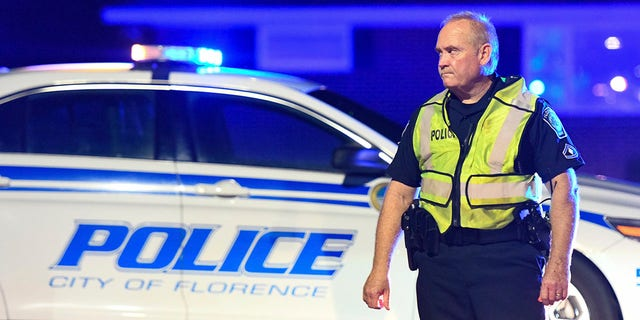 A police officer directs traffic on Hoffmeyer Road near the Vintage Place neighborhood of Florence, S.C., where three deputies and two city officers were shot Oct. 3, 2018.