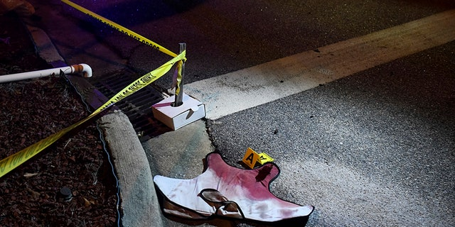 Blood-soaked evidence lies on Saxon Drive in the Vintage Place neighborhood where several members of law enforcement were shot, one fatally, Wednesday, Oct. 3, 2018, in Florence, S.C. (AP Photo/Sean Rayford)