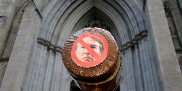 A protester holds a gavel with a slashed-out photo of Brett Kavanaugh in New York, Thursday, Oct. 4, 2018.