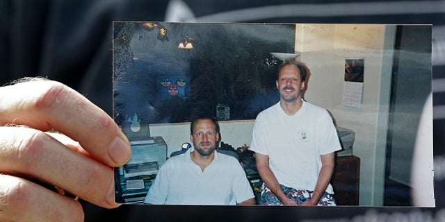 Eric Paddock holds a photo of himself, at left, and his brother, Las Vegas shooter Stephen Paddock.