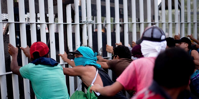 Central American migrants try to force their way through a customs gate at the border bridge connecting Guatemala and Mexico in Tecun Uman