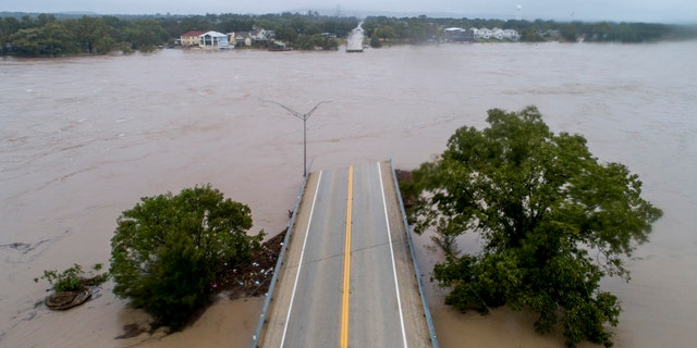 The Llano River flows between the washed out Ranch Road 2900 bridge in Kingsland, Texas.
