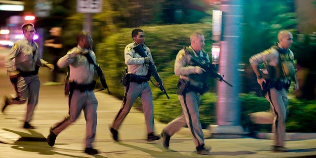 Police running toward the scene of the Las Vegas shooting as it happened one year ago.