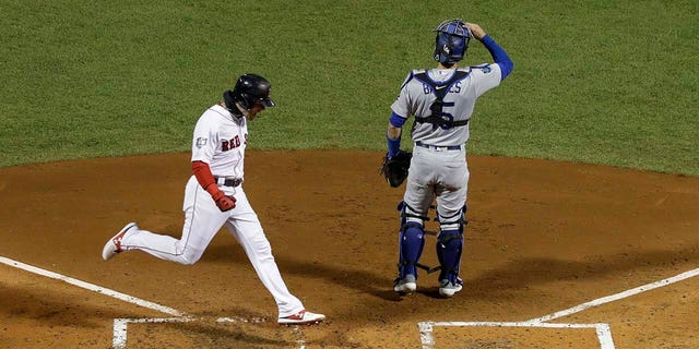 Boston Red Sox's Andrew Benintendi scores past Los Angeles Dodgers catcher Austin Barnes on a hit by J.D. Martinez during the fifth inning of Game 2 of the World Series baseball game Wednesday, Oct. 24, 2018, in Boston. (AP Photo/David J. Phillip)